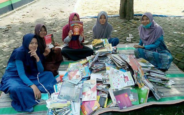 Hanifah Hikmawati (paling kanan) bersama Remaja Islam Watualang (Riswa) merapikan buku-buku untuk perpustakaan desa, Kamis (24/05). Foto-FB/Hanifah